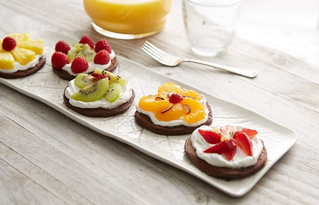 Multiple cocoa pancakes topped with fruit